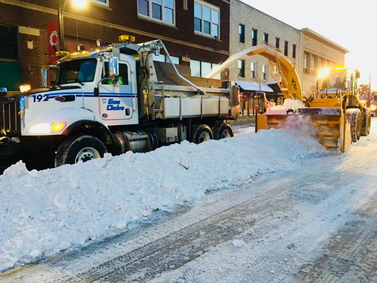 Snow Plow in downtown in evening.