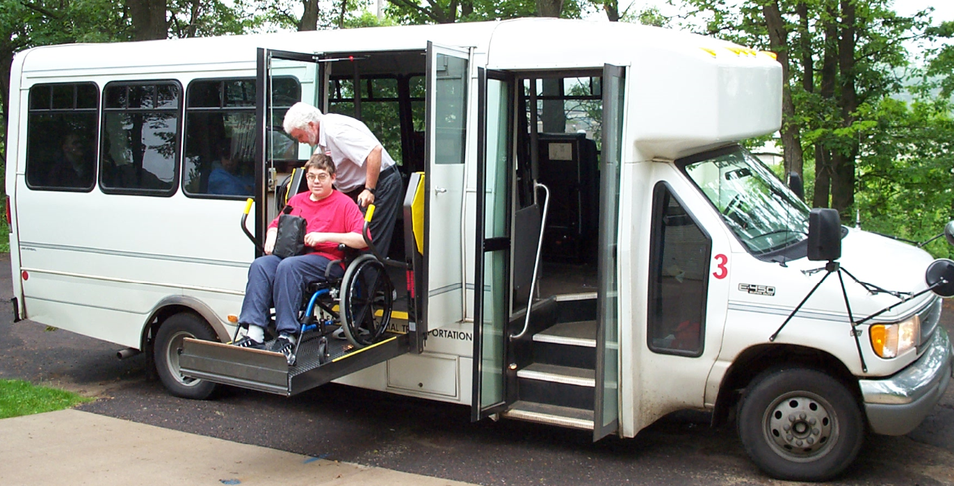 A Passenger in a wheelchair is lowered to street level from the bus