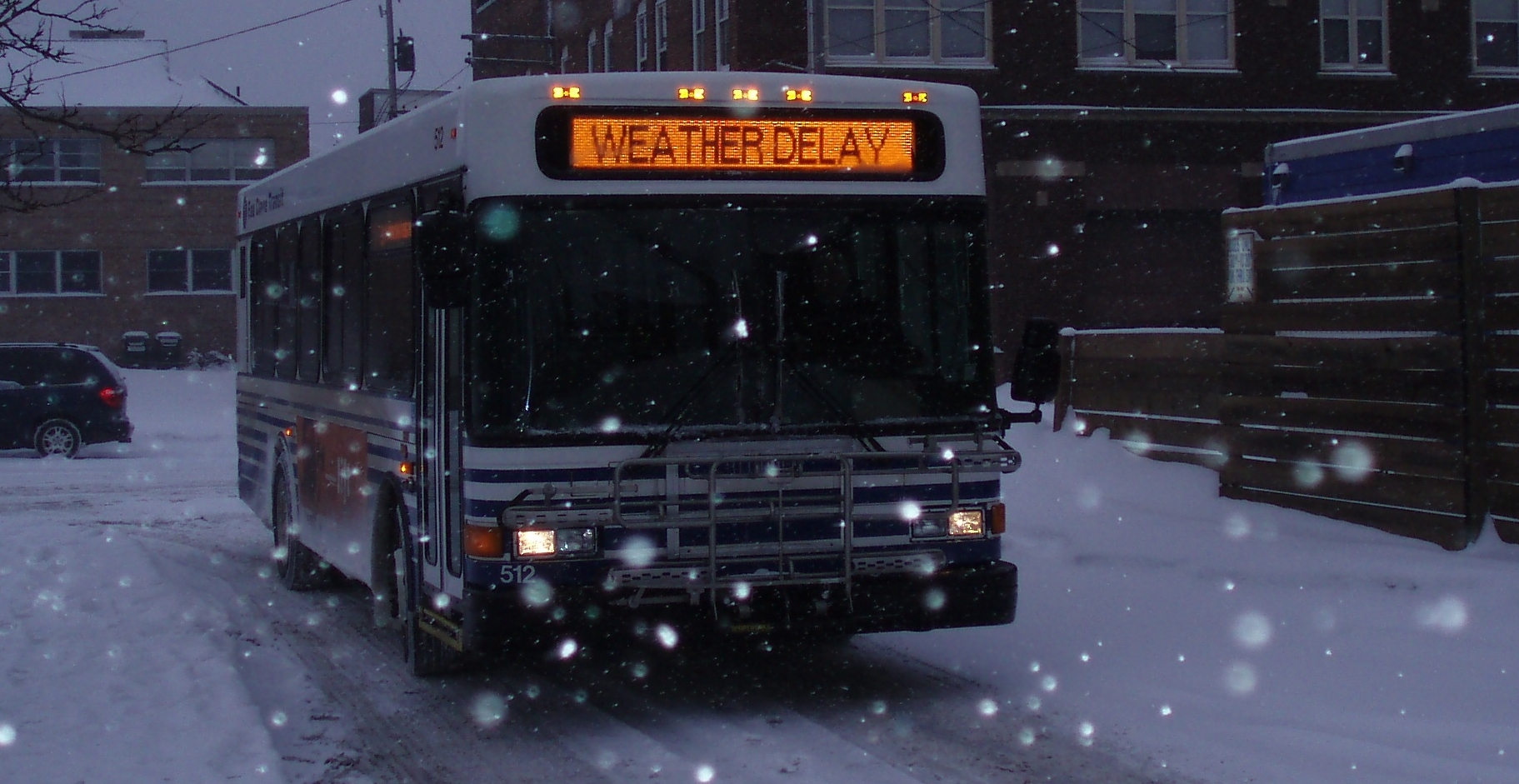"Photo of a bus driving in the snow with an illuminated sign reading ""Weather Delay"""
